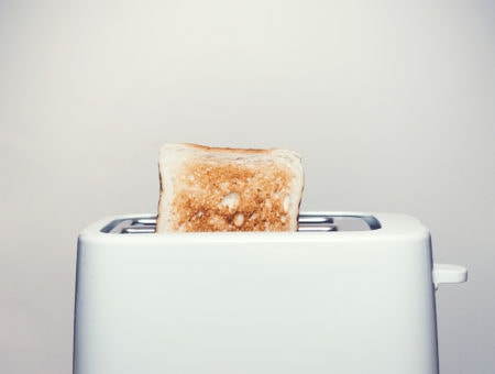 A piece of toast popping out of a white toaster against a gray background.