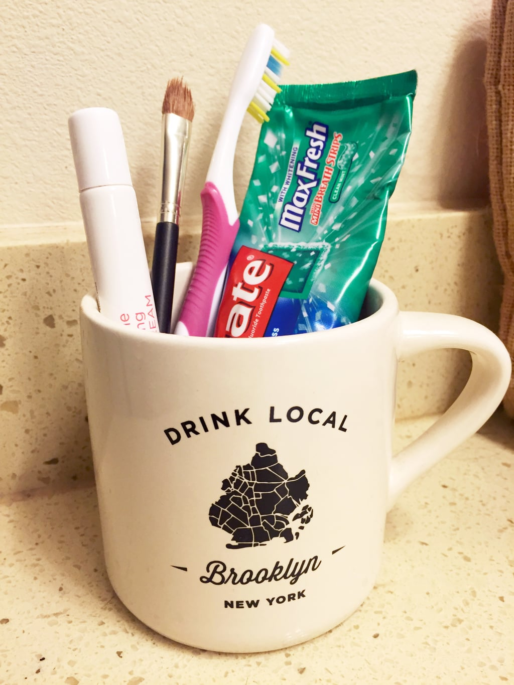 Brooklyn mug used to hold toothbrush and toothpaste in the bathroom