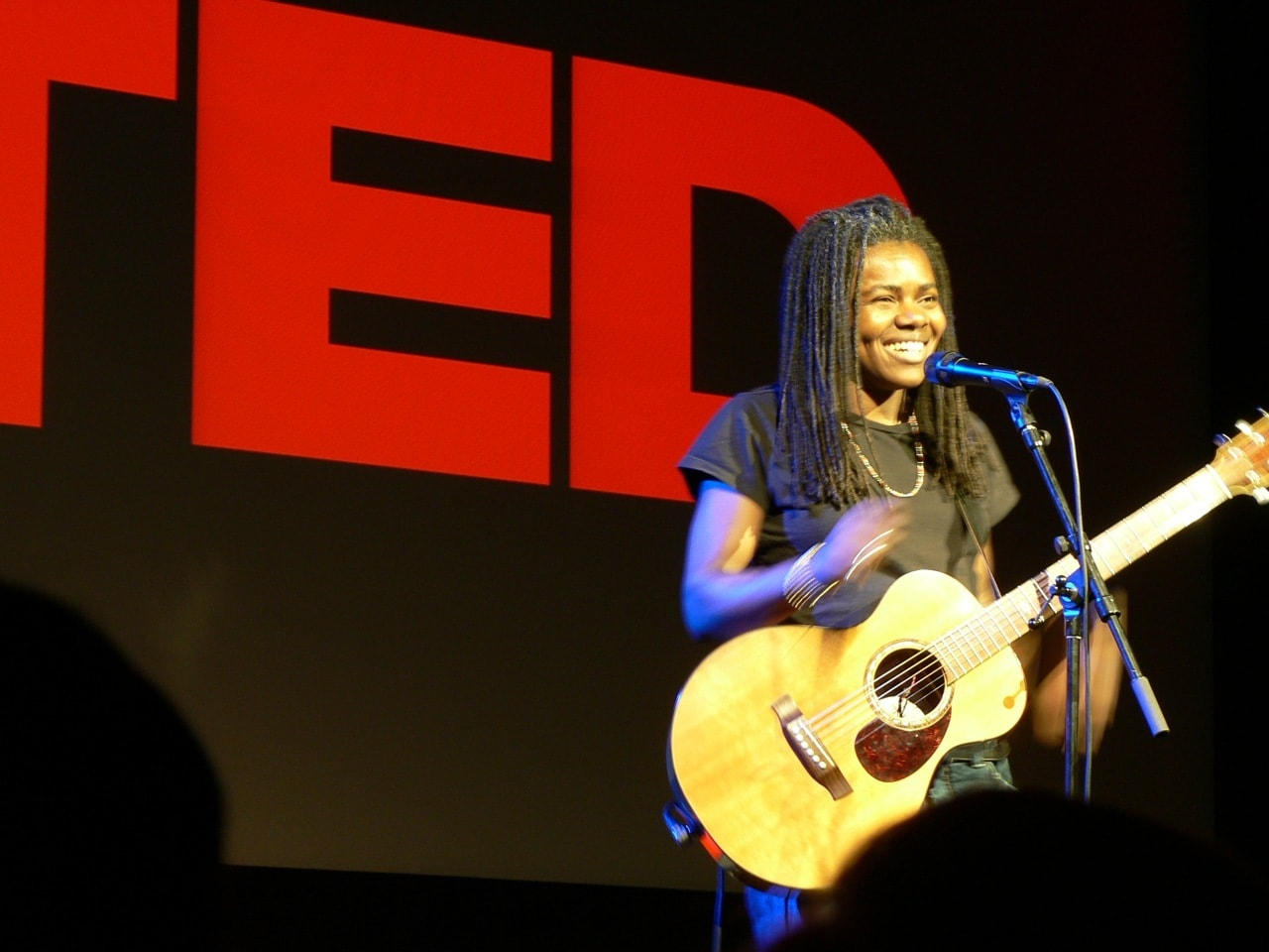 Tracy Chapman on stage at a TED event with her guitar