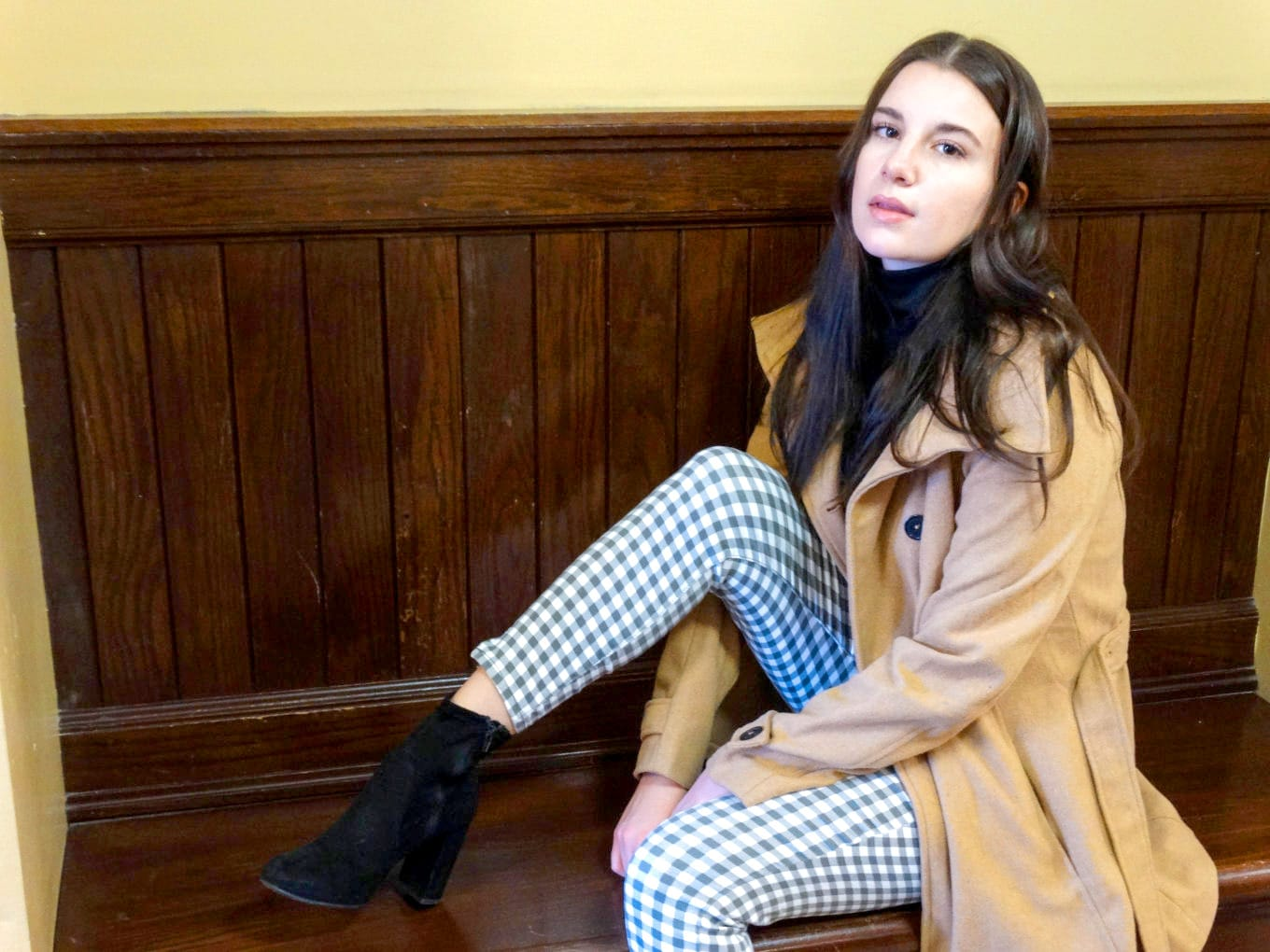 Ariel pairs her checkered pants with black booties and a long camel trench coat.