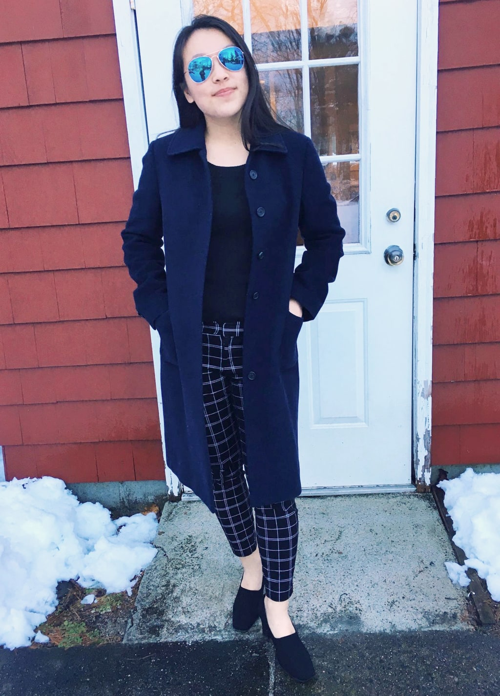 UMass Amherst fashion: Yan Ni sports a black sweater and mid-rise plaid skinny professional pants. She tops off her look with a long navy peacoat and black chunky-heeled shoes.