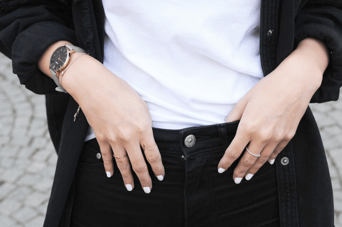 Unique rings and a sophisticated watch on campus at the University of Vienna in Austria. Student Anika wears white nail polish and rocks skinny black jeans and a white tee shirt.