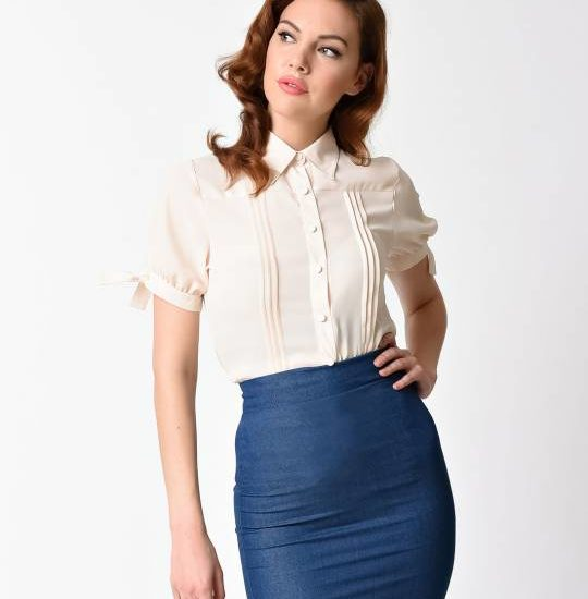 Woman wearing a vintage cream blouse from Unique Vintage and a blue pencil skirt