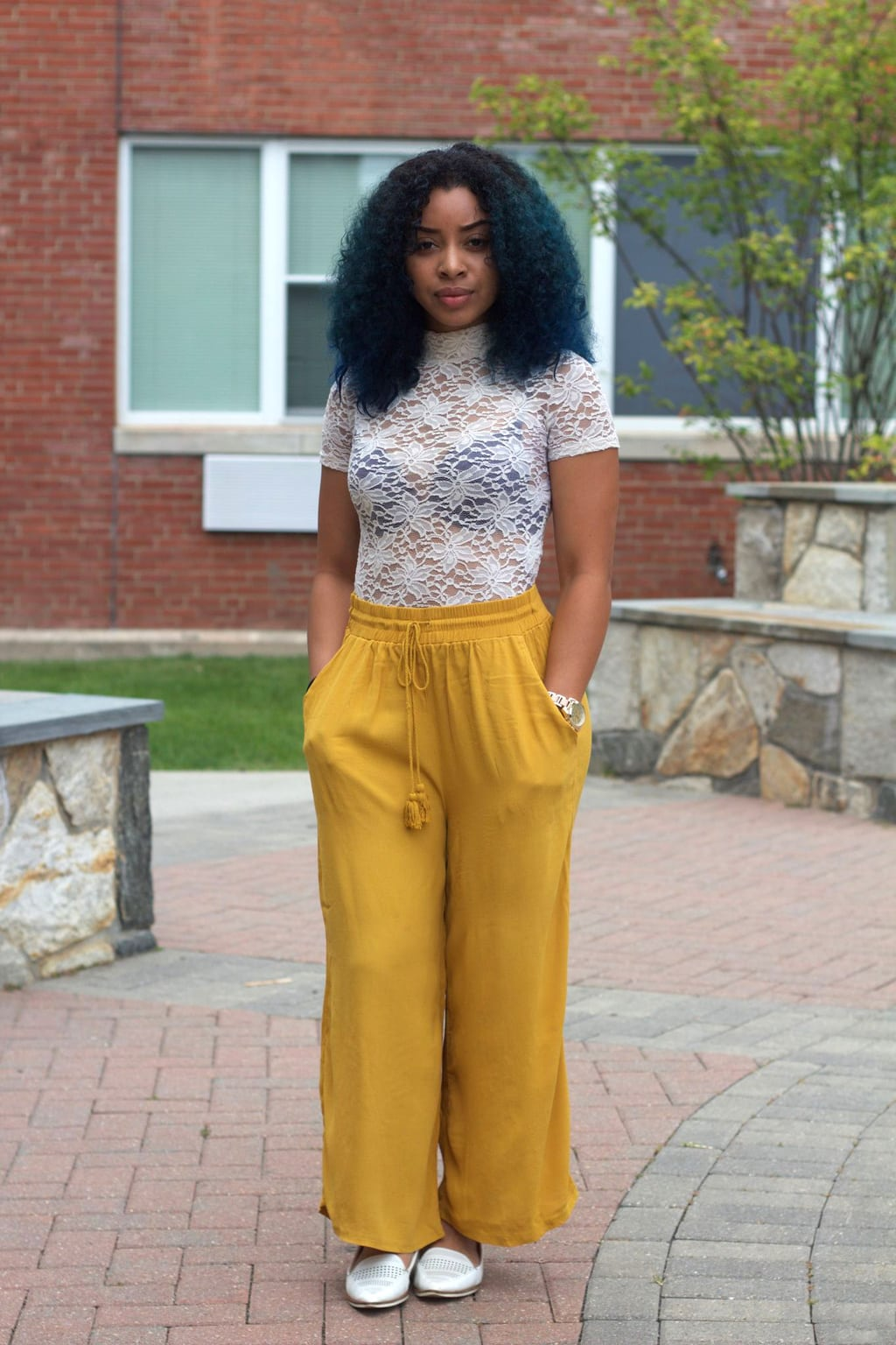 Best lace bodysuit outfit ever: Bold yellow drawstring palazzo pants on University of Bridgeport student Carol, paired with a short sleeve mock neck see-through lace body suit and bright teal hair.