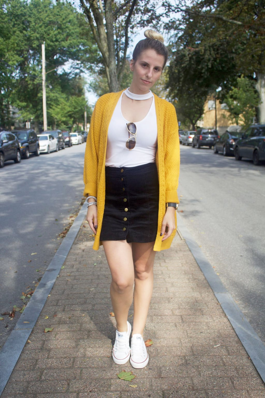 Casual student style: University of Bridgeport student Jessica wears a white top with a chunky mustard cardigan, navy button-up miniskirt, and white Converse sneakers. She tops off her look with some simple aviators and a topknot.