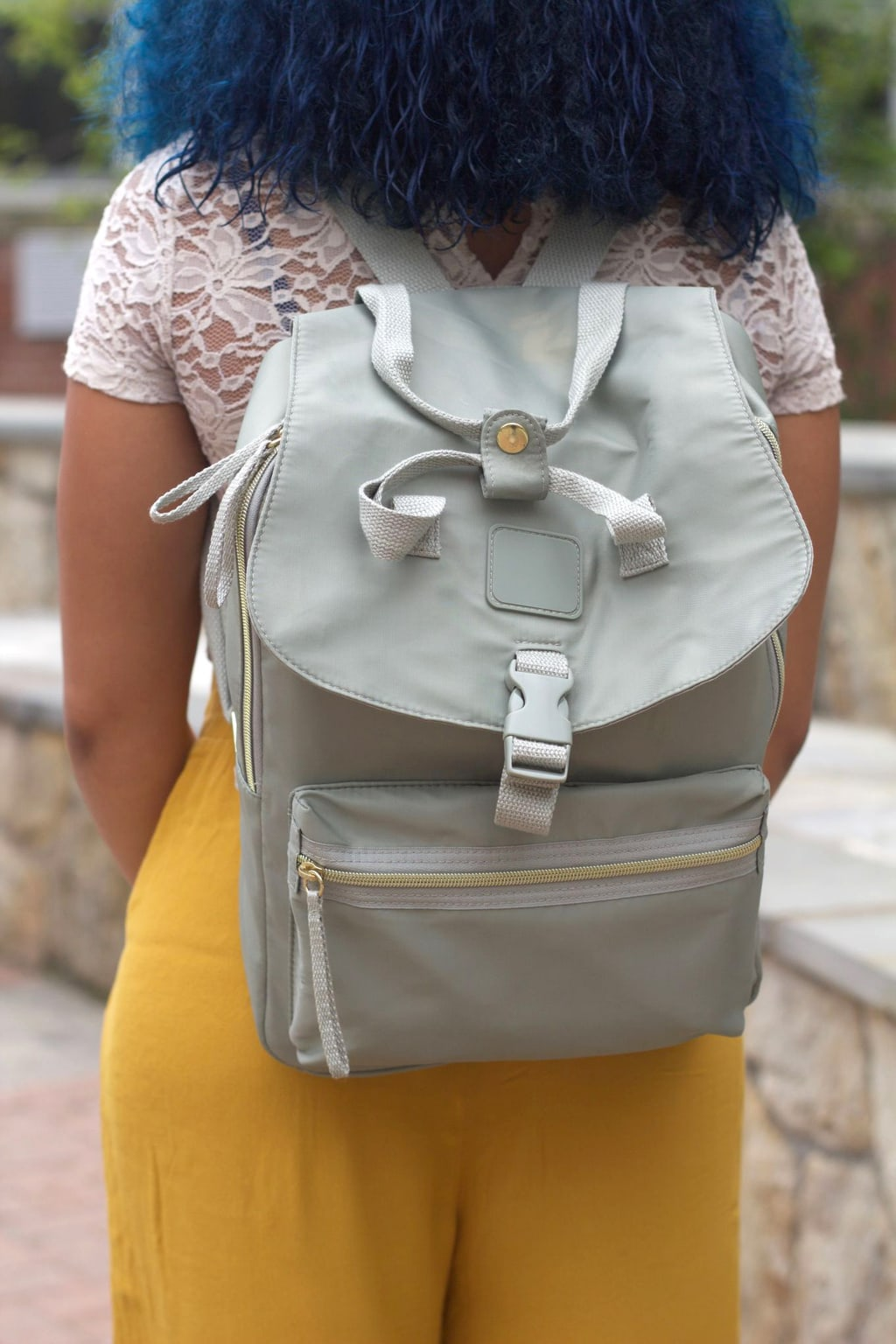 This University of Bridgeport student's fashion forward light grey backpack is trimmed with gold zippers and buttons.