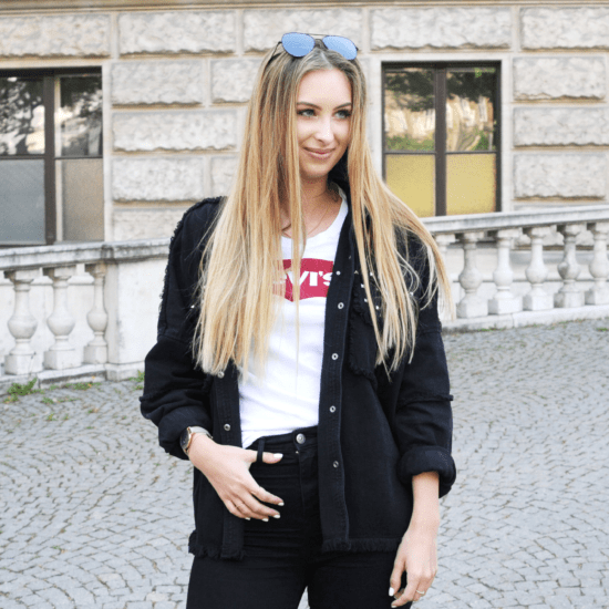 Fashion on campus at the University of Austria - student Anika wears skinny black jeans, an oversized black button down shirt, a white Levi's tee shirt, and aviator sunglasses