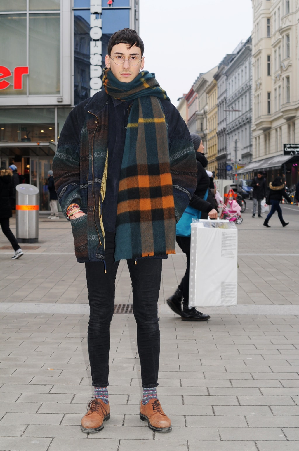 Mens fashion at the University of Vienna in Austria: Plaid coat, plaid scarf, black skinny jeans, oxfords, patterned socks