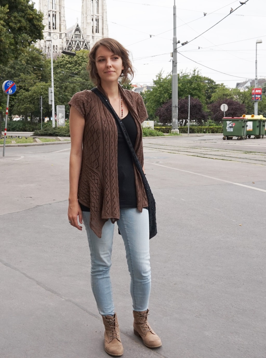 University of Vienna street style: Student wearing a black top, light wash jeans, and a brown cardigan and boots