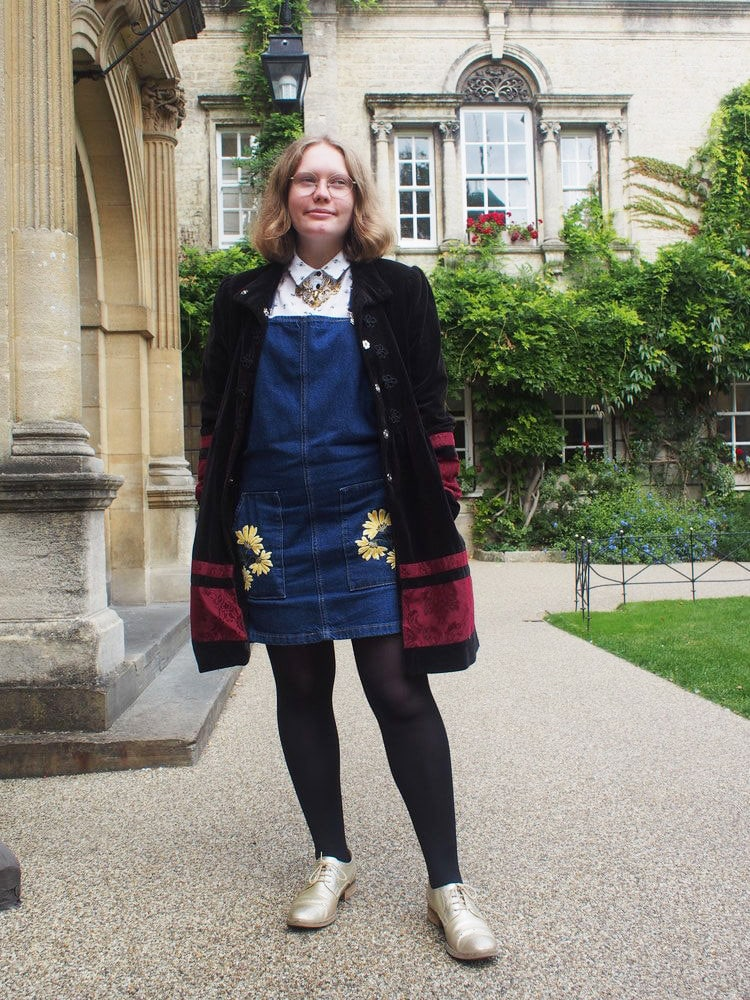 Hannah wears a denim jumper dress with embroidered pockets, a white collared button-up shirt, and a vintage long black coat with maroon detailing.