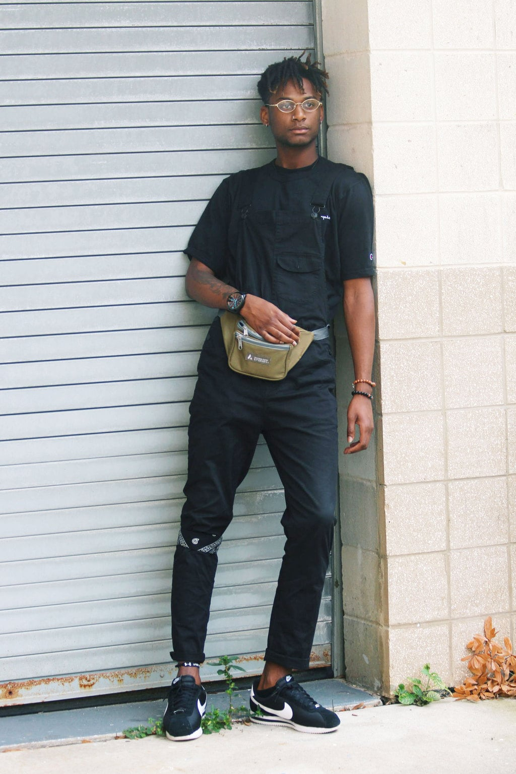 USF Fashion: Mens college fashion at University of South Florida - student Karon wears an all black outfit including overalls, a bandana, a black tee shirt, a fanny pack, glasses, and Nike sneakers