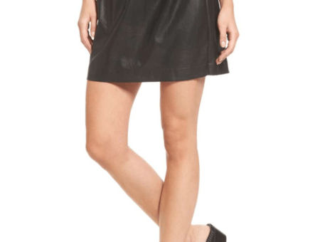 Photo of lower half of woman wearing black faux leather paper bag mini skirt with black-and-white striped t-shirt and black heeled studded mules