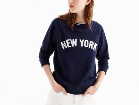 Photo of model wearing navy blue graphic sweatshirt with