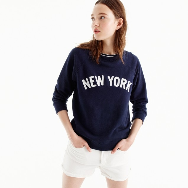 """Photo of model wearing navy blue graphic sweatshirt with """"NEW YORK"""" across the chest in white with white shorts"""