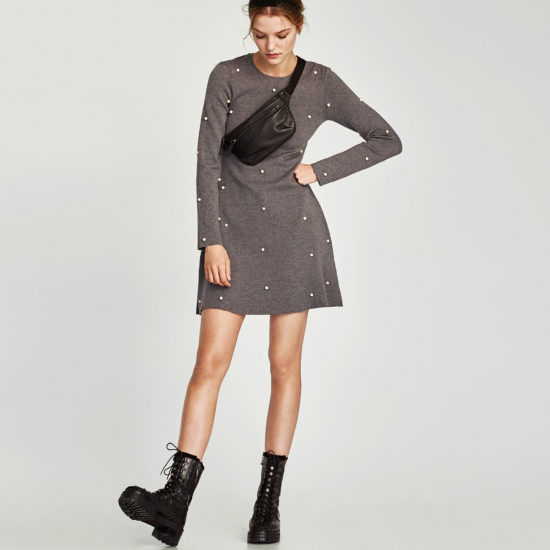 Photo of model standing against light gray background wearing medium-dark gray heathered long-sleeved skater dress with white pearl embellishments, black combat boots, a black pebbled leather fanny pack across one shoulder, and a black headband