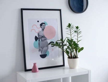 White bookcase with a framed print on top in a white apartment