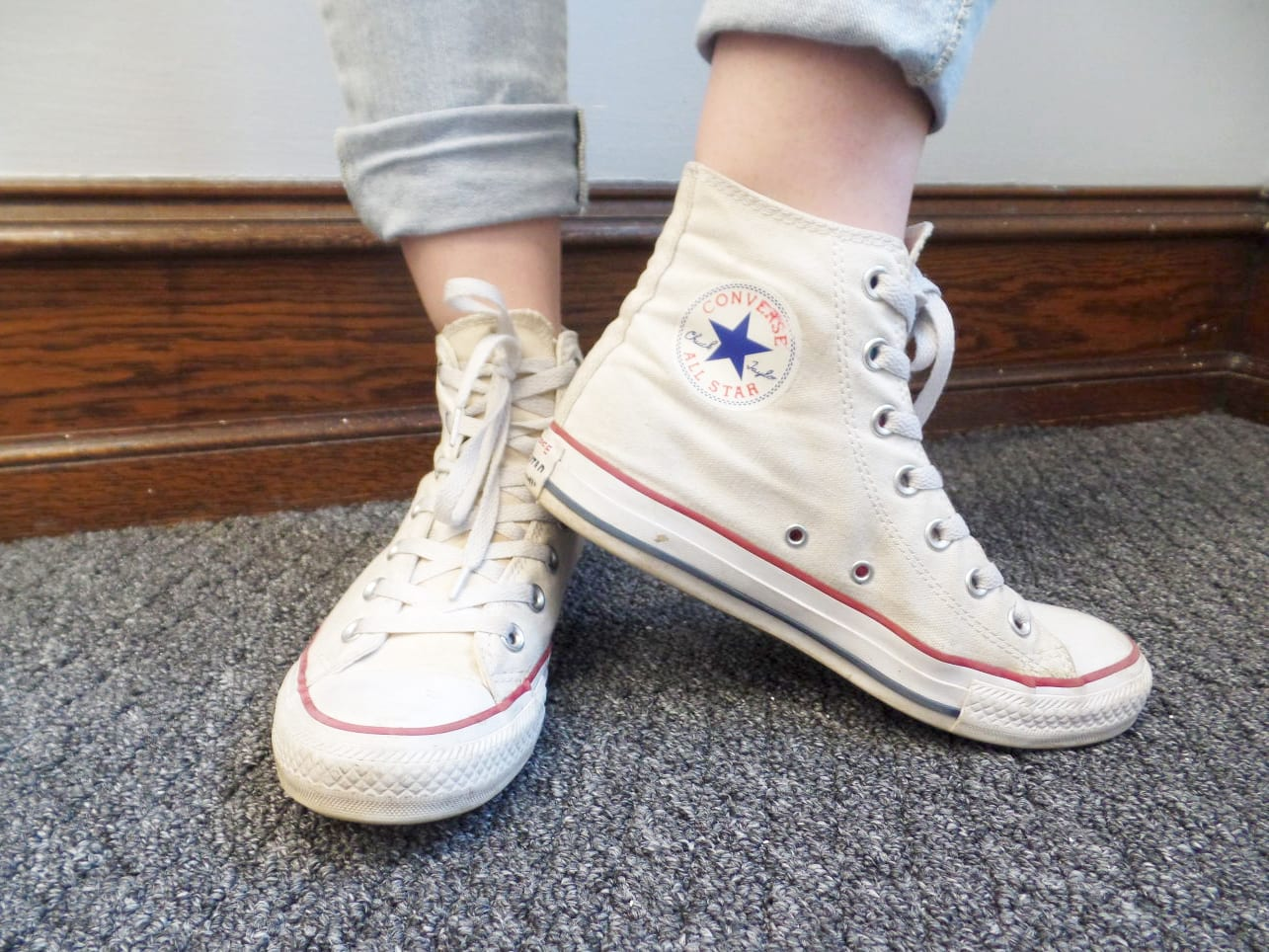 Veronica sports high-top white Converse sneakers with her light-wash jeans cuffed.