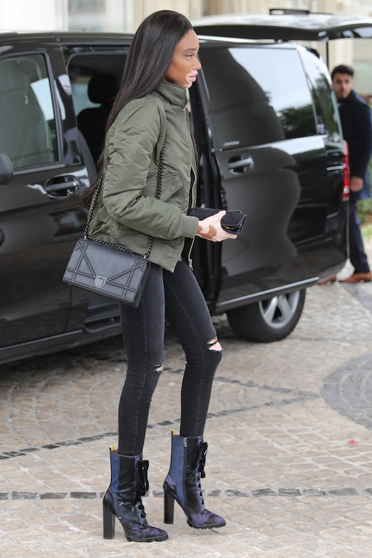 Winnie Harlow wearing an olive green bomber jacket, black crew neck t-shirt, black ripped knee skinny jeans, a black chainlink crossbody bag, and lace-up patchwork mid-calf booties