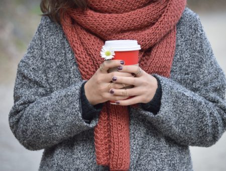 Girl holding holiday Starbucks coffee in winter, wearing grey knit coat and red scarf