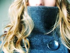Blonde girl wearing a high collar winter jacket