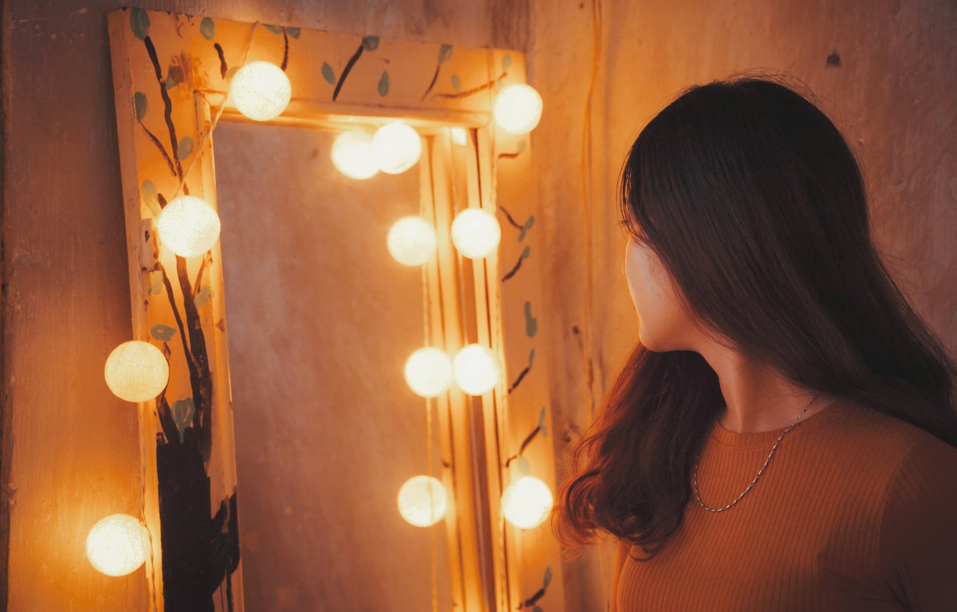 Woman looking at herself in a lighted mirror
