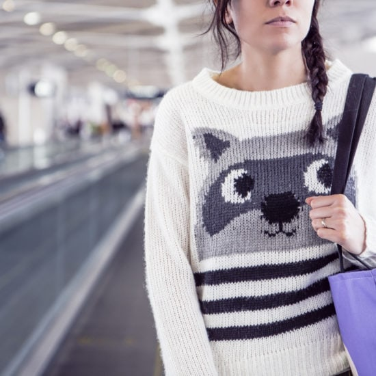 Woman at the airport on a moving sidewalk wearing a raccoon sweater and carrying a purple tote bag