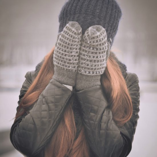Woman wearing mittens and a quilted leather jacket, covering her face in the winter snow