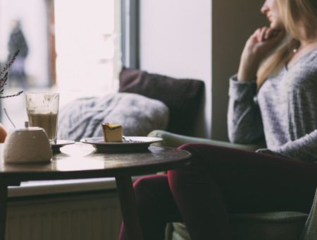 Woman looking out window in cafe with cake and coffee