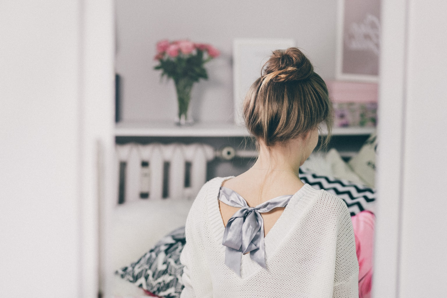 Woman in her room wearing a bow back sweater