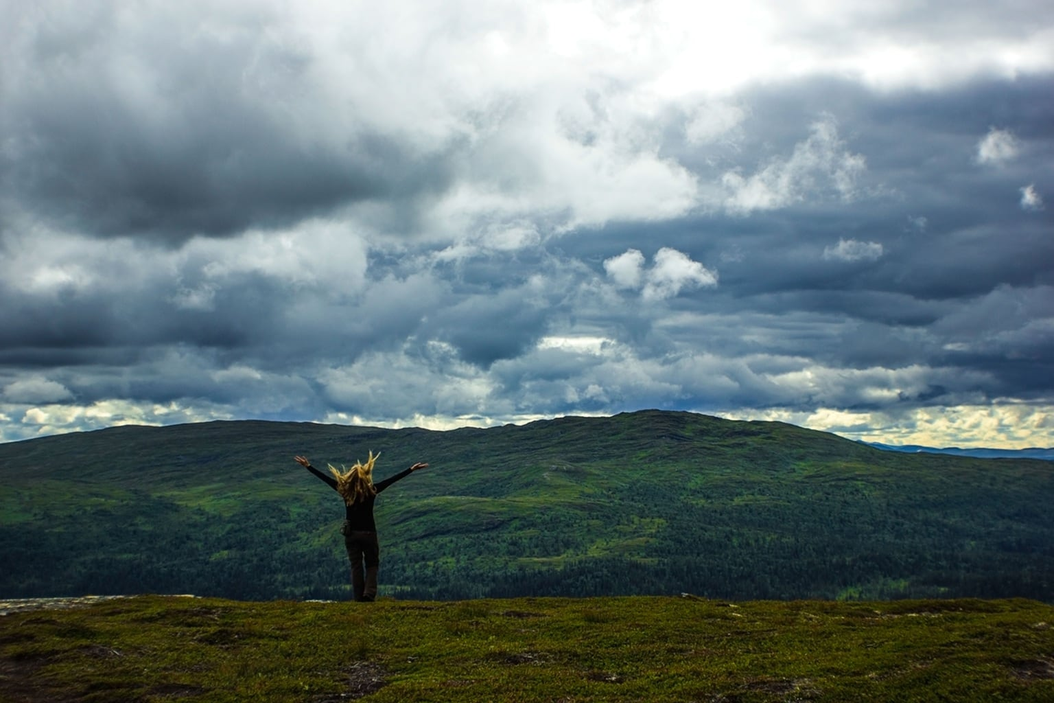 Woman on a hilltop with her arms outstretched under a cloudy sky