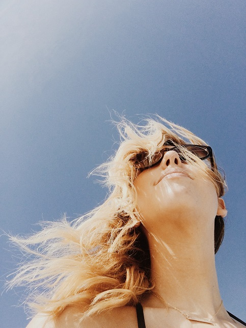 Woman in Sunglasses Looking Out at Blue Sky
