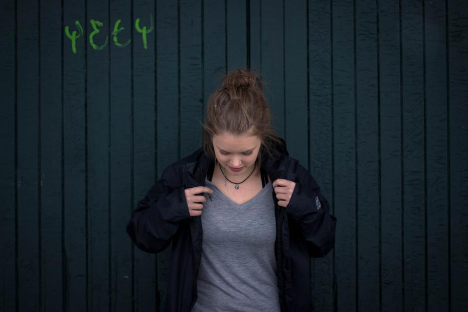 Woman against dark wall in grey t-shirt and black jacket