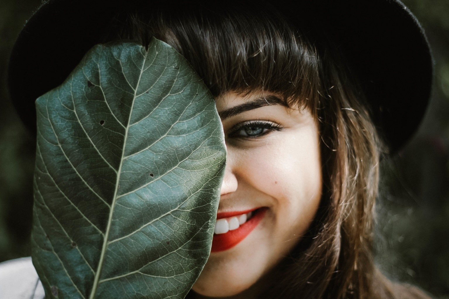 Woman wearing red lipstick and covering half of her face with a leaf