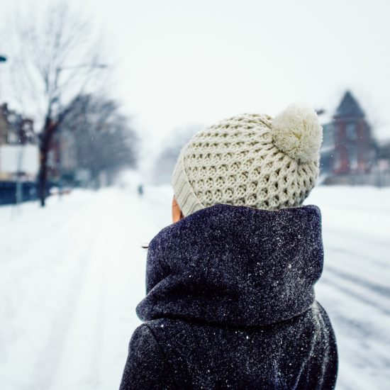 Woman wearing a beige winter knit hat in the snow