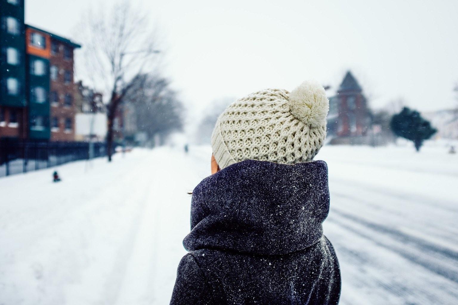 Woman wearing a beige winter knit hat in the snow