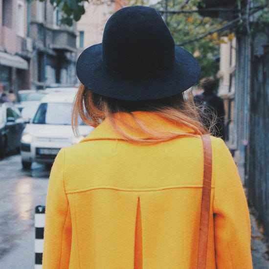 Woman wearing a yellow coat and black rounded hat