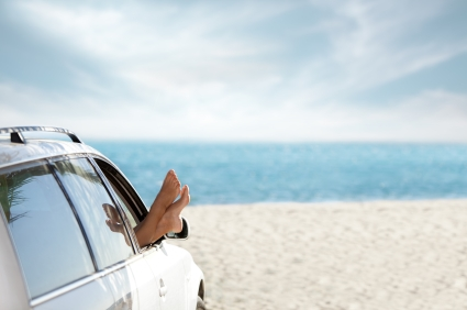 Woman at the beach with her feet out of the car window