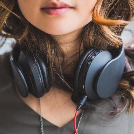 Woman with black headphones around neck