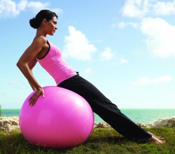 Woman working out near the beach on a pink exercise ball