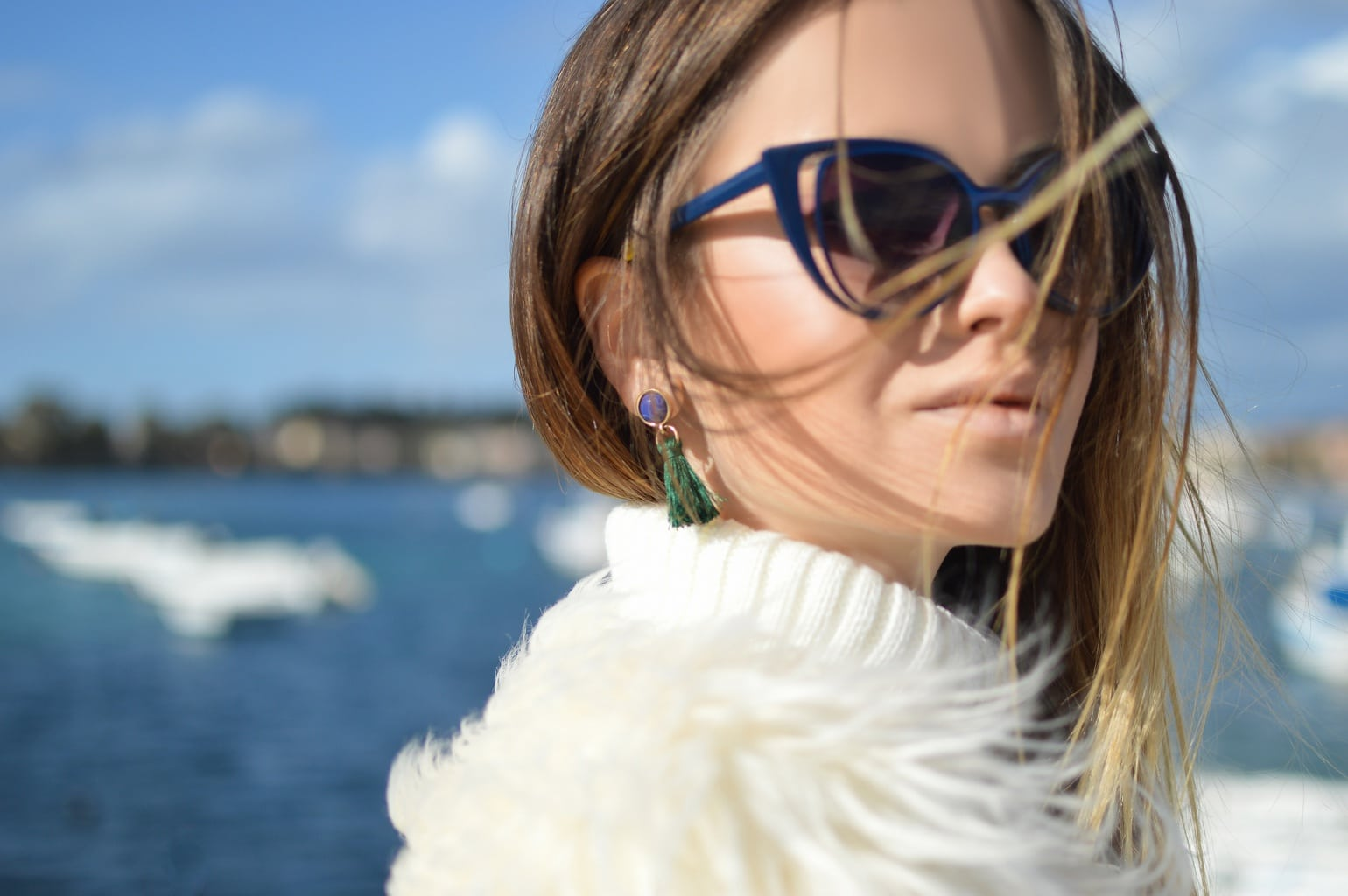 Single woman standing in front of the ocean, wearing sunglasses and a fur jacket