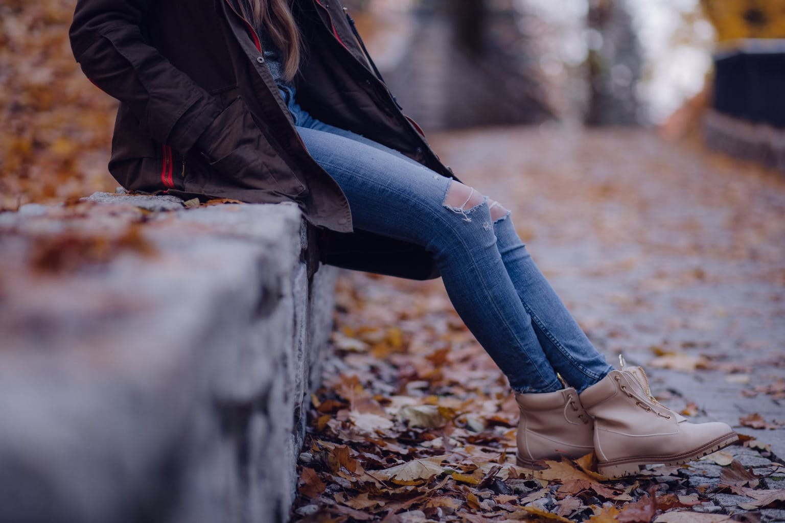 Woman sitting on a ledge in fall wearing blue jeans, boots, and a black jacket