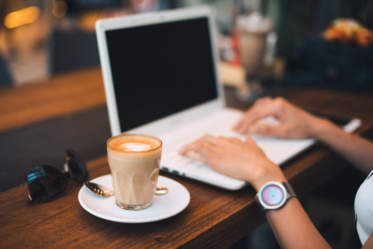 Girl wearing a watch working on a computer with a coffee next to her.
