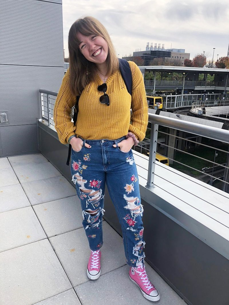 West Virginia University student Maria wears a chunky mustard knit sweater, floral embroidered and ripped jeans, and high-top pink Converse sneakers.