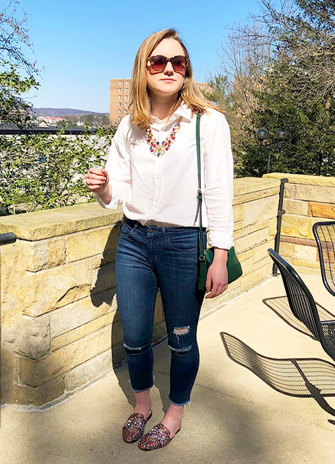 This West Virginia University student wears a basic white linen button-down shirt tucked into a pair of basic dark skinny jeans with distressed knees. She sports them with flat jeweled mules from Target and a green Kate Spade over-the-shoulder purse. She finishes off her look with a statement gold necklace full of red, baby blue, and navy blue jewels.