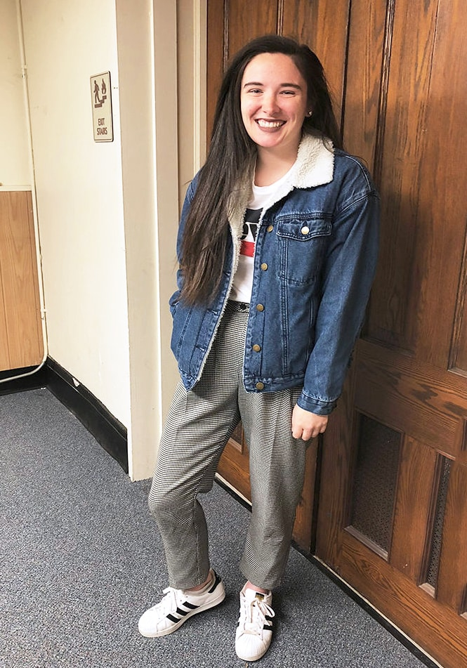 West Virginia University student Rachel wears a casual daytime look that consists of a basic white Levi's tee tucked into grey loose checkered slacks, an oversized denim jacket lined with shearling, and white Adidas allstar sneakers.