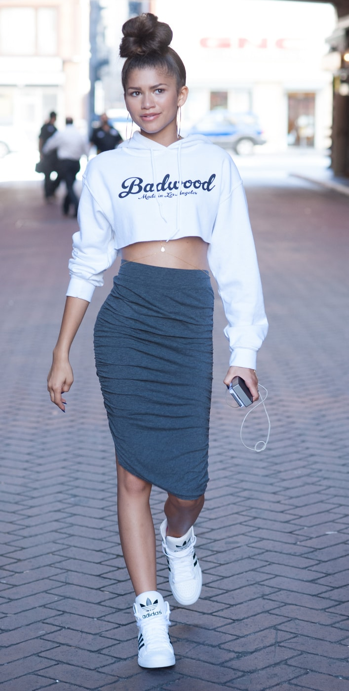 Zendaya, cropped white sweatshirt, high raunched midi-skirt, white high top adidas.