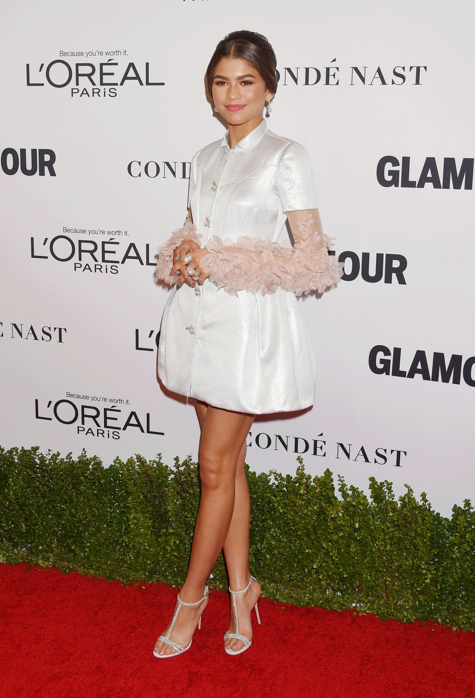 Zendaya at the 2016 Glamour Women of the Year awards wearing a white bubble hem dress with floral sleeves, diamond rings on every finger, and strappy silver heels