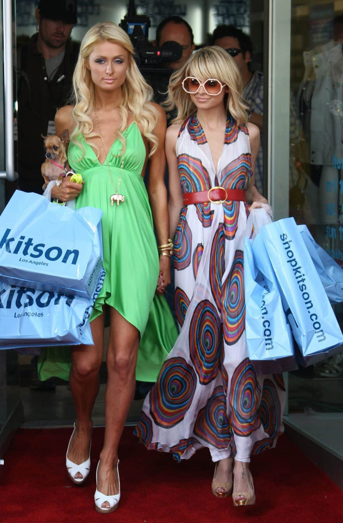 Nicole Richie and Paris Hilton holding hands and shopping bags.