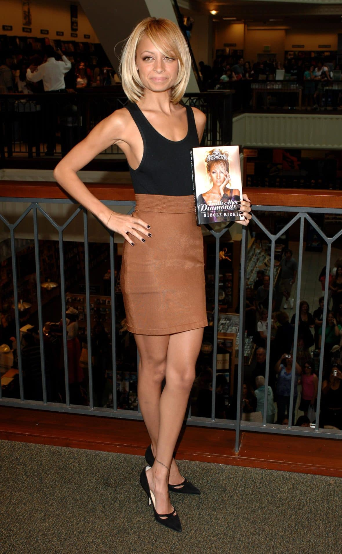 Nicole Richie in a black tank top and camel brown skirt holding a book.