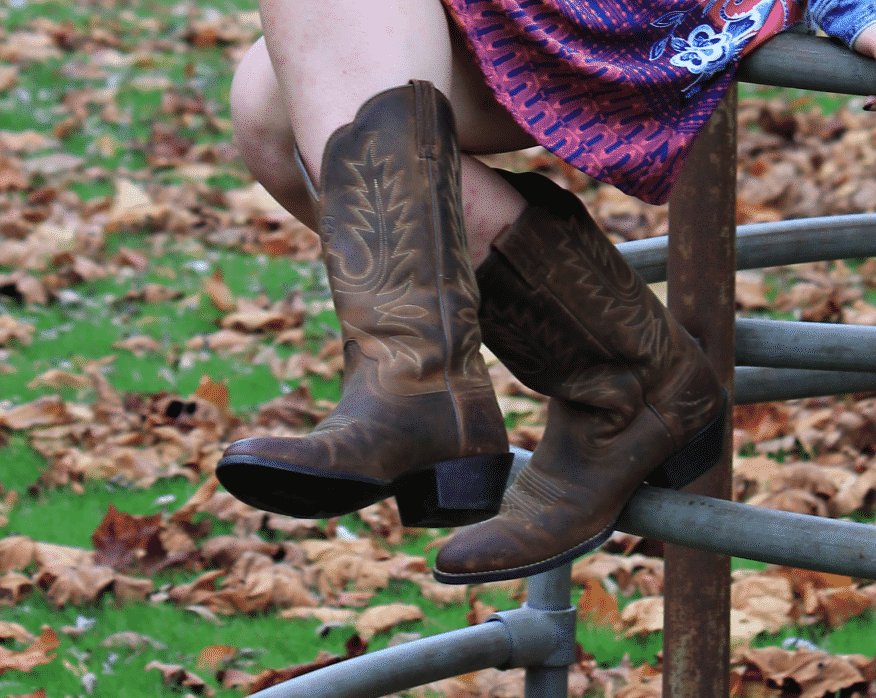 This GVSU student wears distressed dark brown cowboy boots with light-brown stitching.
